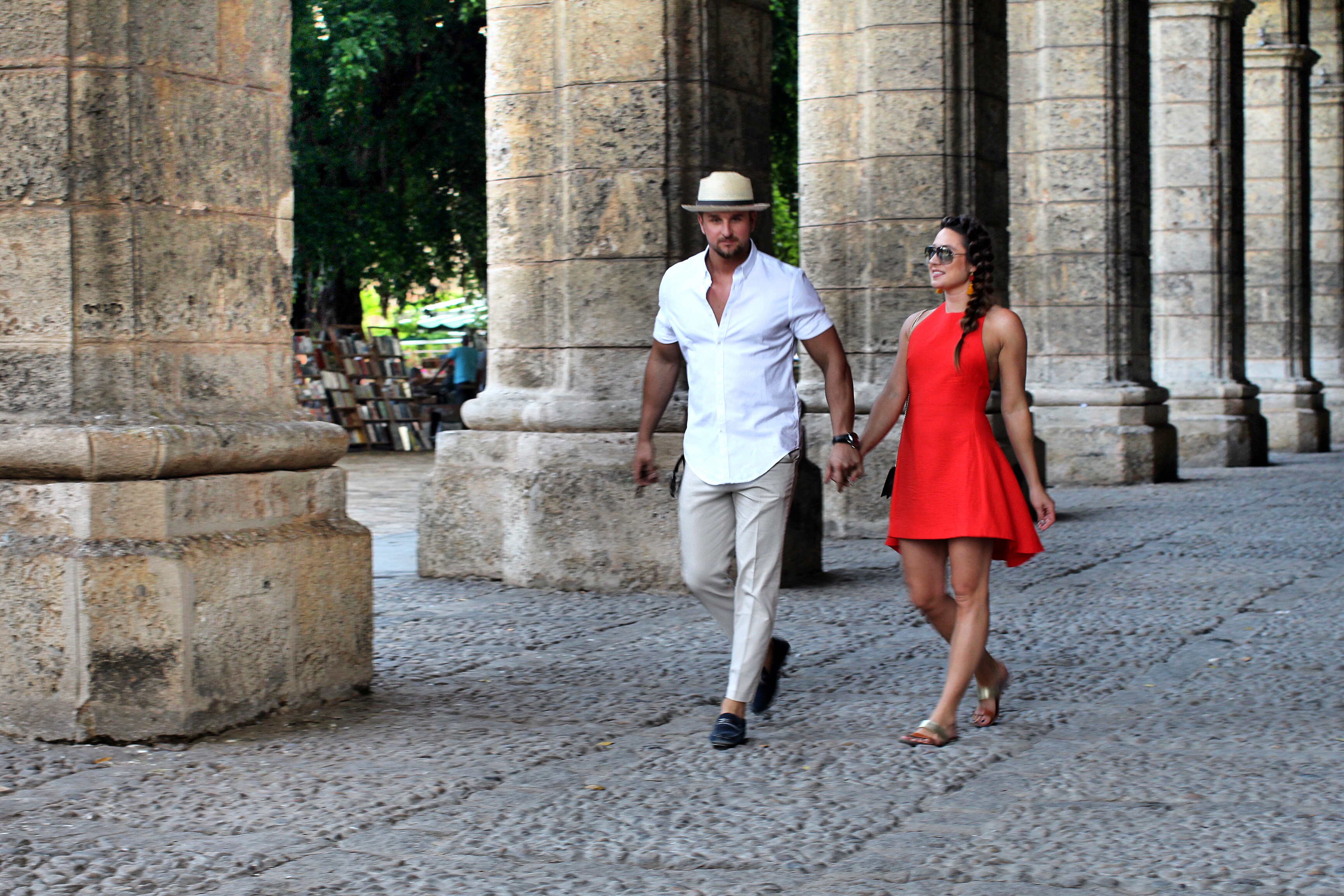 holding-hands-girl-boy-red-dress-fedora-columns-streets-havana-cuba